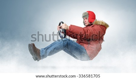 Man driver in a red cap with a steering wheel. Driving a car in a snowstorm - stock photo