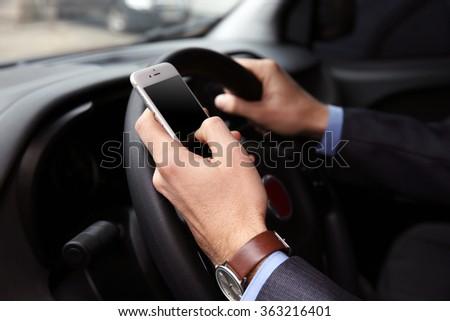 Man driver using smart phone in car - stock photo