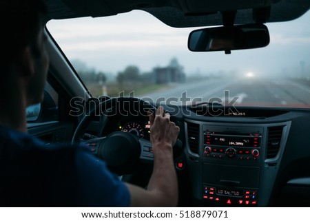 Man driving a car in fog. Back view