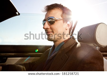 Man driving a convertible car - stock photo