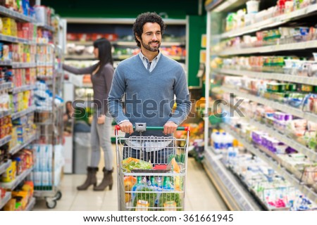 Man driving a shopping cart in a supermarket - stock photo