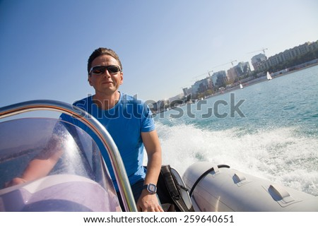 man driving an inflatable motor boat at a speed rushes to the sea - stock photo