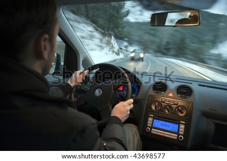 Man driving car in snowed mountain road. - stock photo