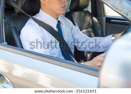 man driving car, steering wheel of a car, focus at finger. Hand fastening a seat belt, wearing safety belt driving