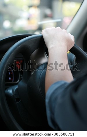 Man driving car with his hand on the steering wheel