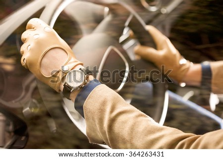man driving, detail shot, hands on the steering wheel, wearing leather men gloves