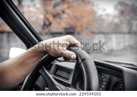 Man driving his car. Hands holding the wheel. Toned photo.