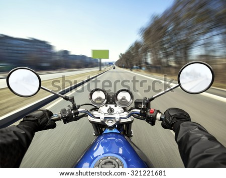 Man driving on moto on big speed on asphalt road - stock photo