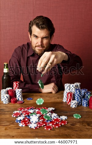man dropping poker chips on to pile for a bet, focus on chips - stock photo