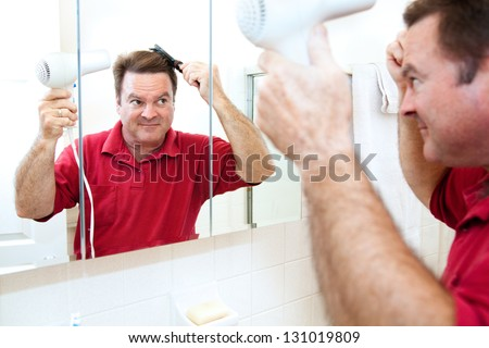Man drying his hair with a hand held blow dryer in the bathroom mirror.
