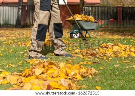 Man during autumn cleaning works on the backyard, - stock photo