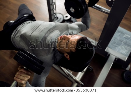 Man during bench press exercise at gym club - stock photo