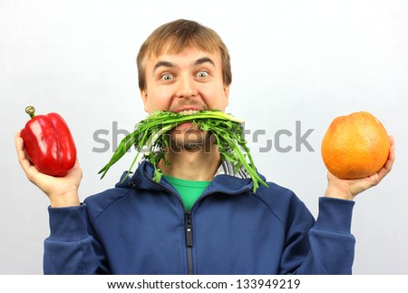 man eat green-stuff and hold in his hand fresh pepper and grapefruit - stock photo