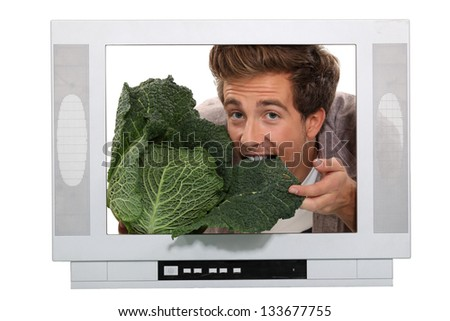 Man eating a cabbage inside a television