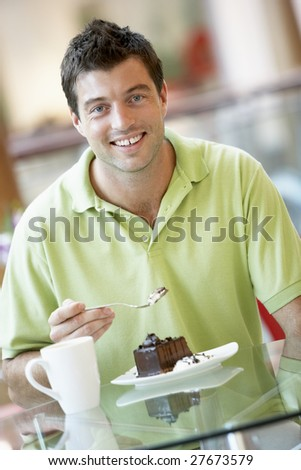 Man Eating A Piece Of Cake At The Mall - stock photo