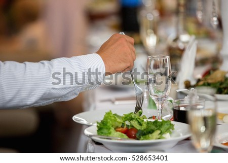man eating a salad in a restaurant