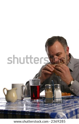Man eating a sandwich at a diner or cafe - stock photo