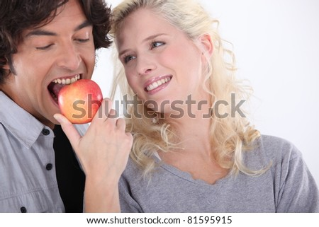 Man eating apple next to smiling woman - stock photo