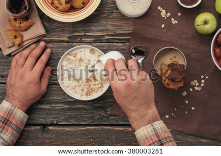 Man eating breakfast oatmeal with cookies and coffee on a dark wooden table. Healthy lifestyles concept, top view - stock photo