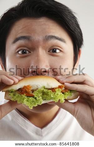 man eating burger on the white background - stock photo