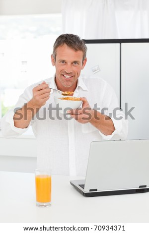 Man eating cereal while he is working on his laptop - stock photo