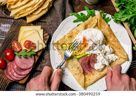 Man eating crepe galette with ham, avocado, soft white cheese and poached egg on white plate. Sliced yellow cheese, pastrami, cherry tomatoes, green salad and stack of crepes on side. Top view - stock photo