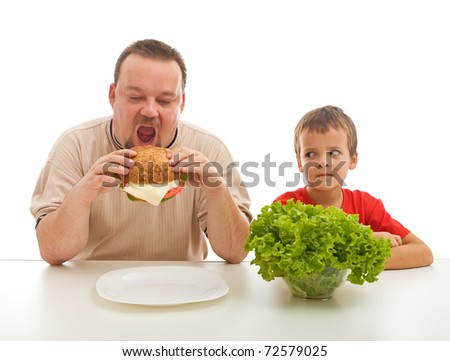Man eating hamburger and boy with salad watching - healthy eating teaching by example concept - stock photo