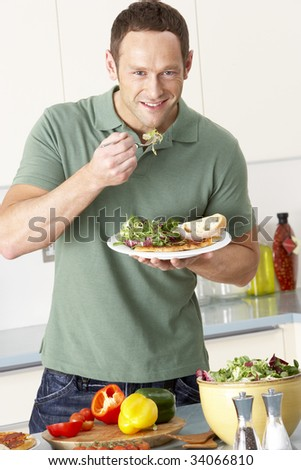 Man Eating Meal In Kitchen - stock photo