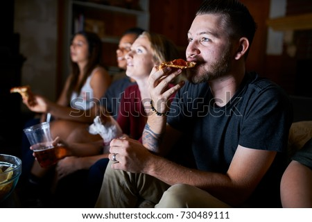 man eating pizza while watching tv at night with friends
