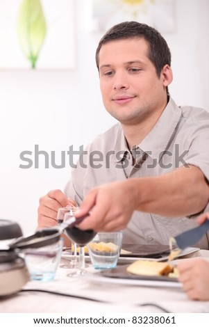Man eating raclette - stock photo