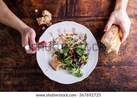Man eating rucola salad - stock photo