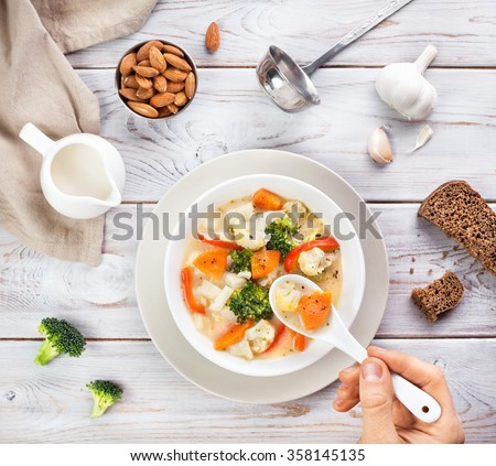 Man eating vegan soup with vegetables and almond milk on wooden white background - stock photo