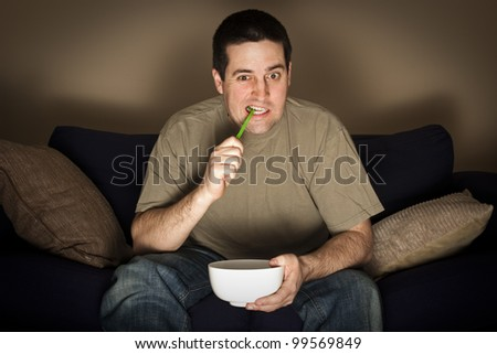 Man eats a green snake while watching TV intently