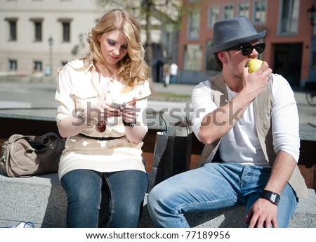 Man eats an apple while his girlfriend looking at her mobile phone - stock photo