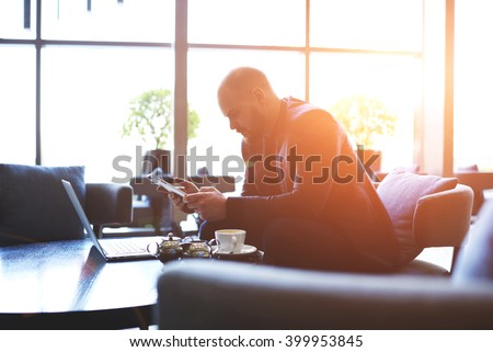 Man economist developing a scheme for the company for the future by using touch pad and laptop computer. Male professional banker is analyzes currency transactions with digital tablet and net-book - stock photo