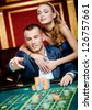 Man embraced by pretty girl throws the chip on the roulette table - stock photo