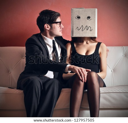 man embraces beautiful woman with a box on her head sitting on the couch - stock photo