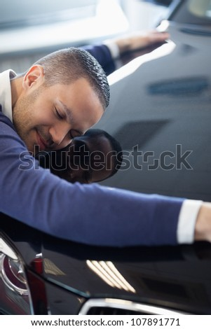 Man embracing a car in a garage - stock photo