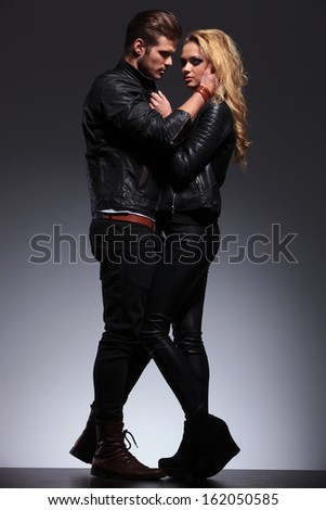 man embracing and looking with passion at his girlfriend on a gray studio background - stock photo