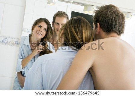 Man Embracing his Woman In Bathroom,seen in the reflection of a mirror - stock photo