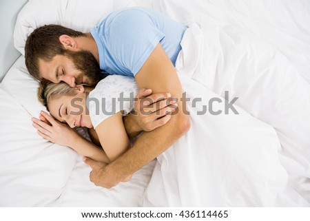Man embracing woman while sleeping on bed at bedroom - stock photo