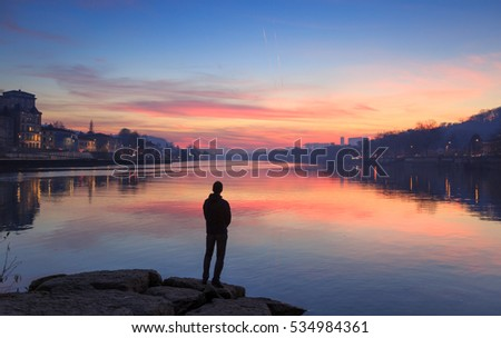 Man enjoying a colorful dawn at the Saone river in the city of Lyon.