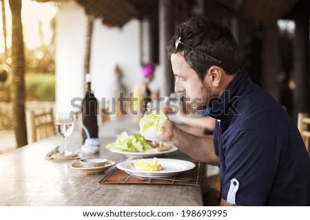 Man enjoying a meal with chopsticks in vietnamese restaurant - stock photo