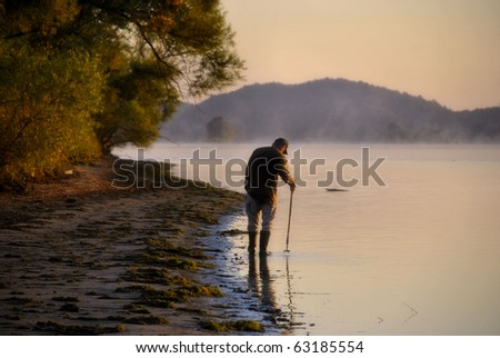 Man enjoying a morning walk along the Tennessee River on a slightly foggy day, mountain in the distance