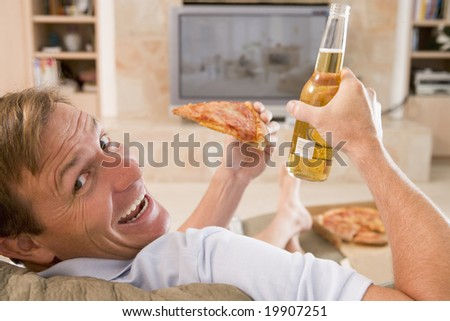 Man Enjoying Beer And Pizza In Front Of TV - stock photo