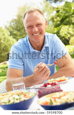 Man Enjoying Meal In Garden - stock photo
