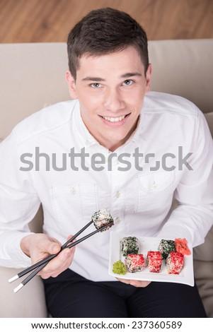 Man enjoying sushi. Cheerful young man is eating sushi and looking at the camera. Top view. - stock photo