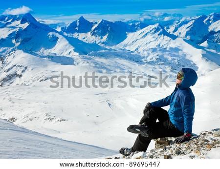 man enjoying the view in snowy mountains - stock photo