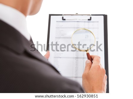Man Enlarging Content On Clipboard With Magnifying Glass - stock photo