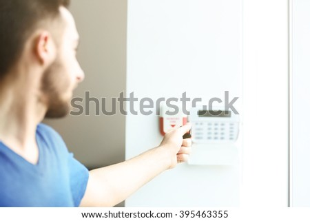 Man entering code on security system keypad indoors - stock photo